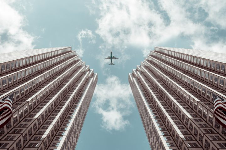 plane flying over skyscrapers